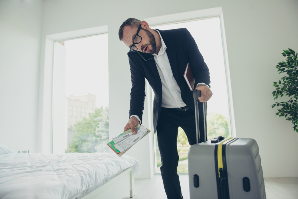 man in his hotel room on the phone and carrying a map and suitcase