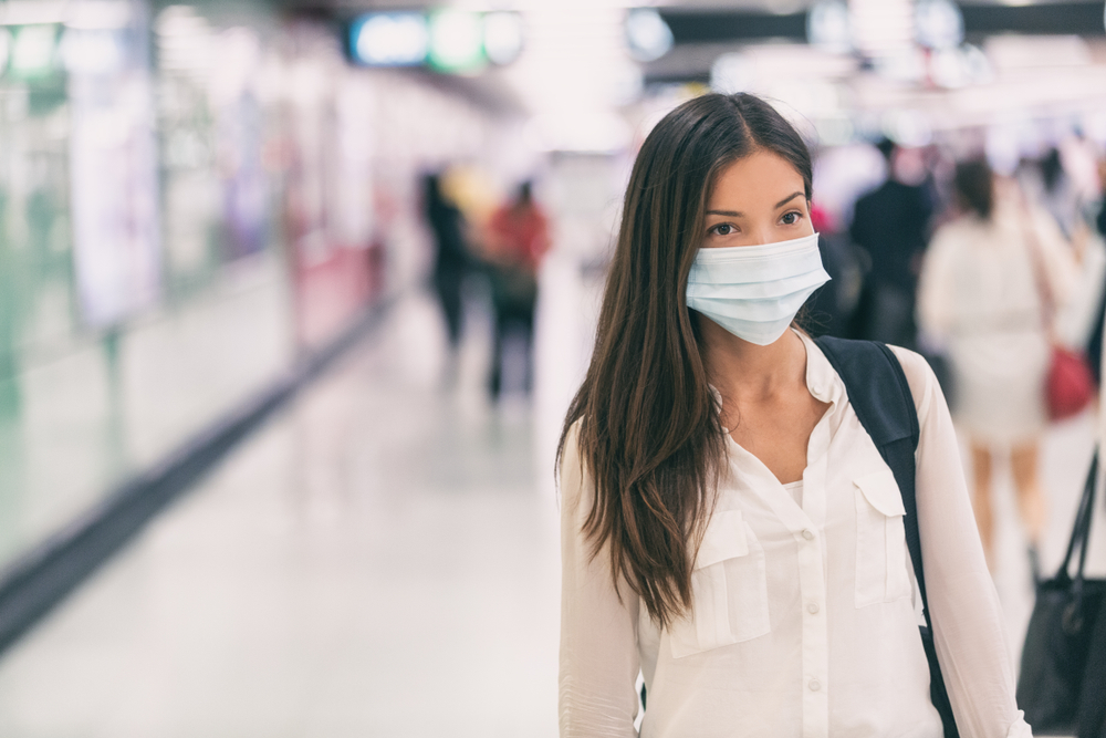 woman in a n airport wearing a facemask