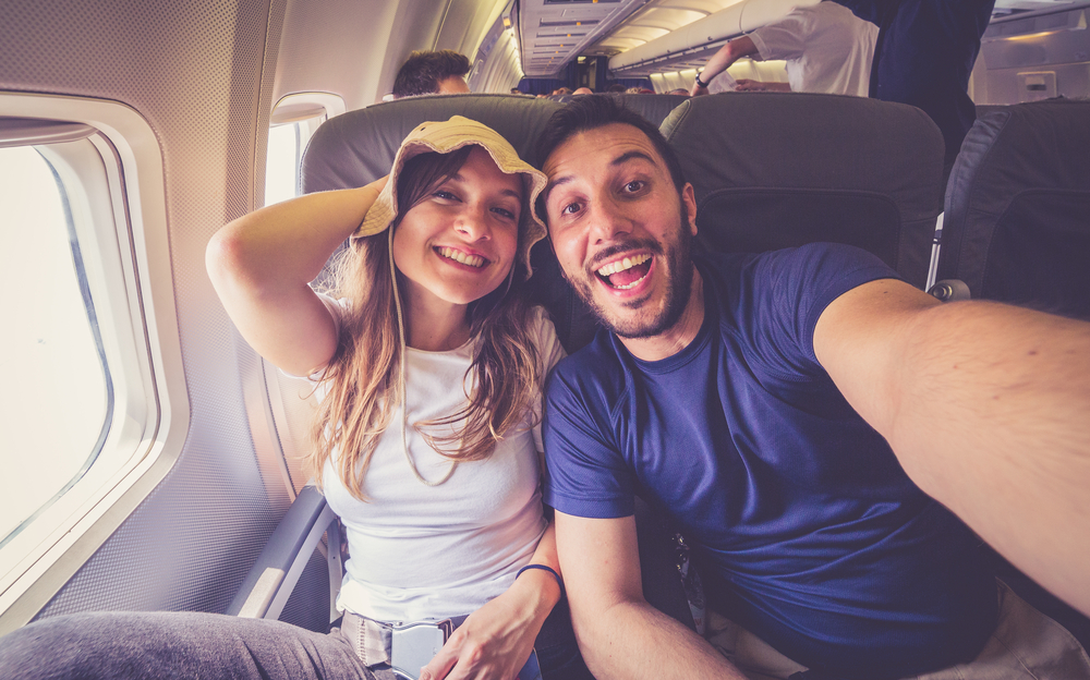 man and woman taking a selfie on a plane getting ready to travel